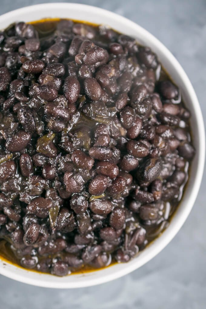 Close-up overhead view of cooked Instant Pot black beans in a bowl, showing that the beans are juicy and not dry