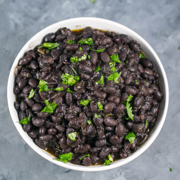 Overhead view of a bowl of pressure cooked black beans with additional fresh coriander scattered in the background