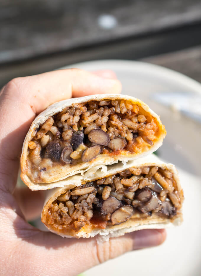 Photograph of a vegan burrito after being microwaved and then sliced in half, showing the rice and beans on the interior
