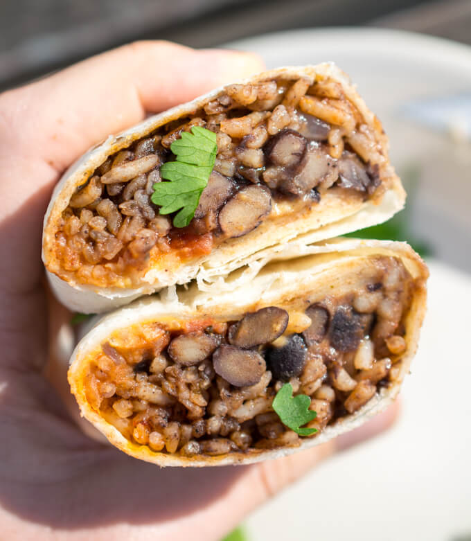 Inside of a vegan burrito, with black beans, tomato salsa, and orange rice visible, as well as chopped fresh cilantro