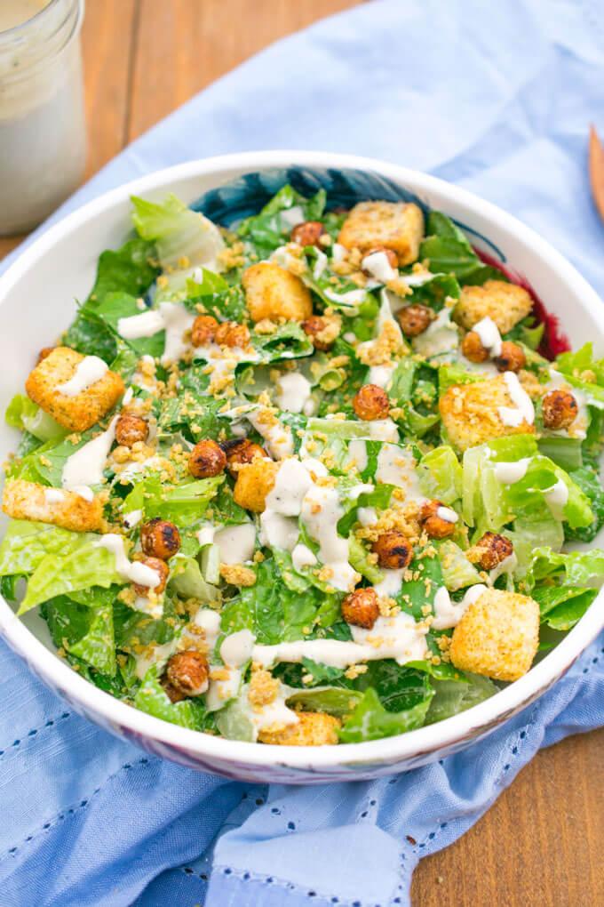 Vegan caesar salad in a serving bowl, garnished with hemp parmesan, croutons, and several circular drizzles of white vegan caesar dressing.