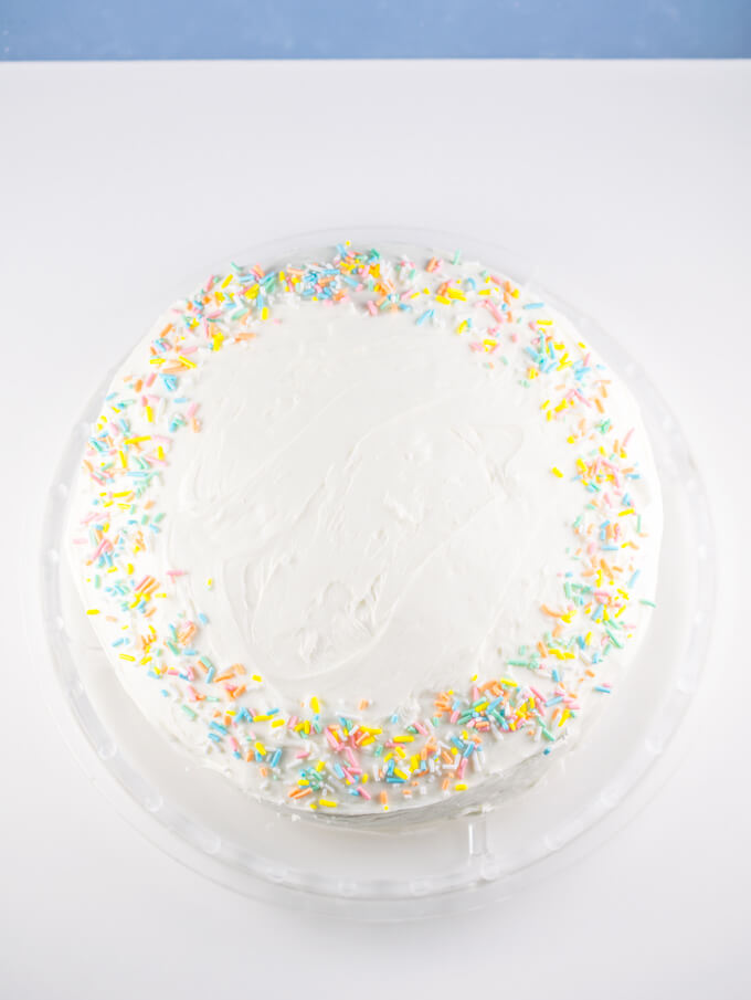 Overhead view of a vegan white cake decorated simply with plain vanilla icing and colorful funfetti birthday sprinkles around the edges.