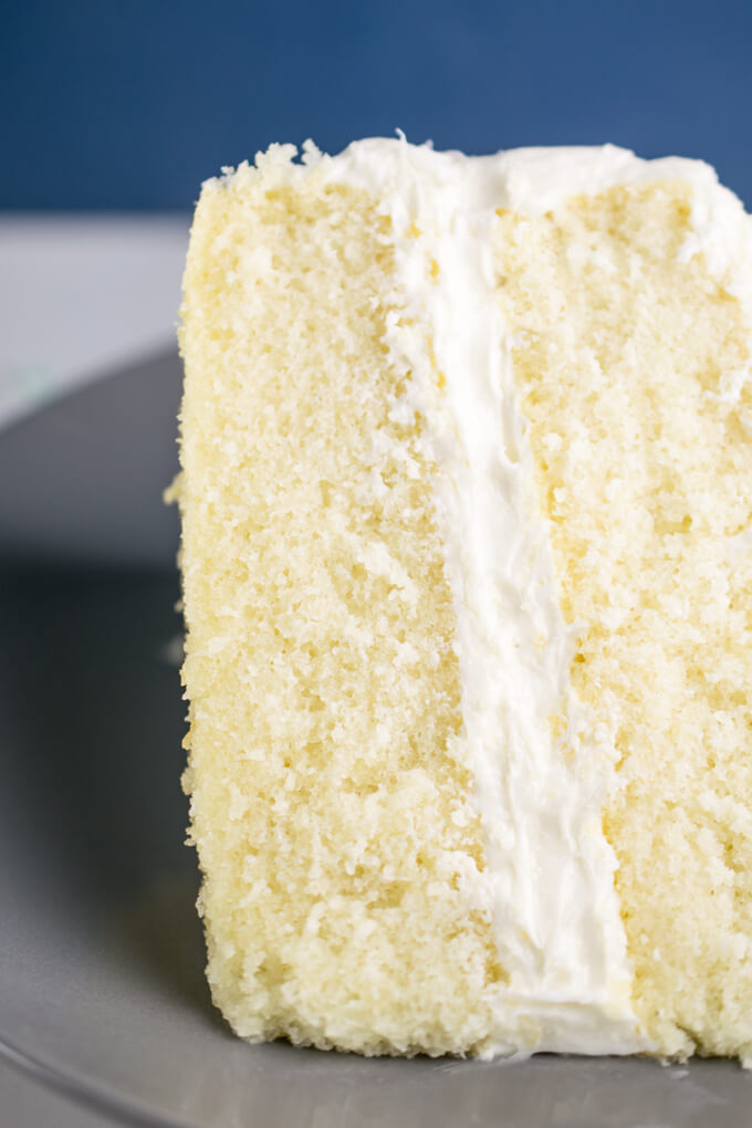 Close-up of the inside of a slice of vegan white cake. A small, tender, even crumb is evident, with a pale yellow vanilla color to the cake.