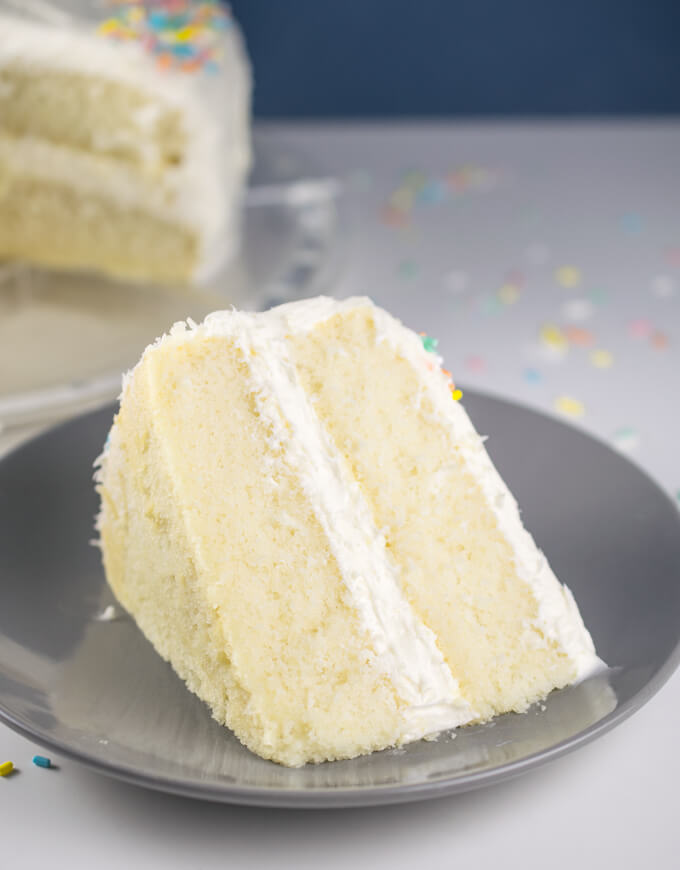 A slice of vegan white cake on a plate, showing tall, fluffy layers of pale golden cake between layers of white frosting.