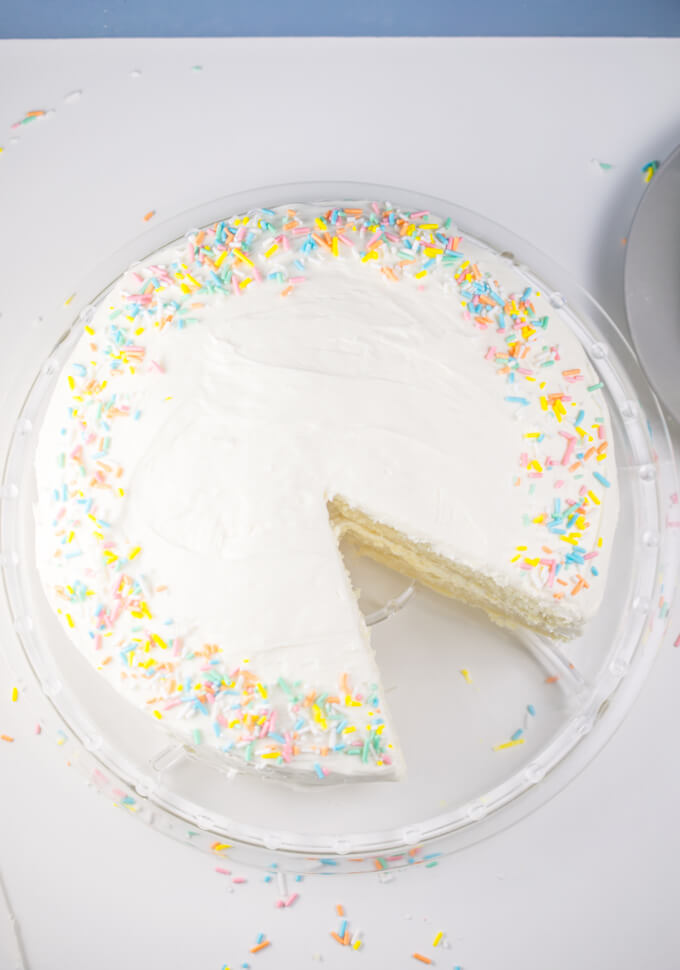 Overview of a vegan white cake with one slice cleanly removed from it.