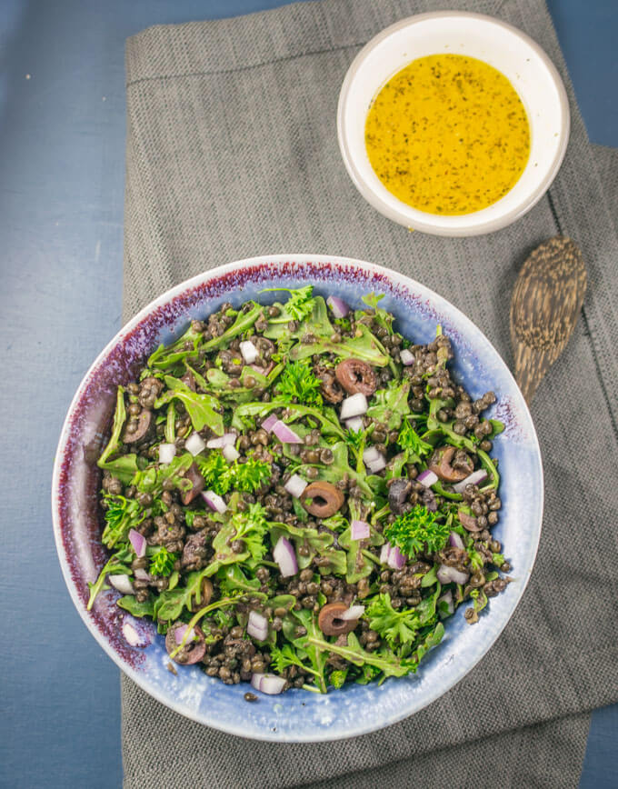 Overhead view of a bowl of lentil salad on a gray napkin with a smaller bowl of yellow lemon vinaigrette in the background