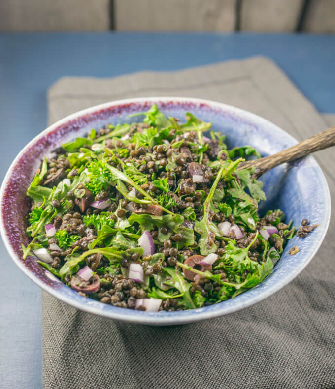 Arugula and lentil salad in a ceramic bowl, garnished with chopped red onions