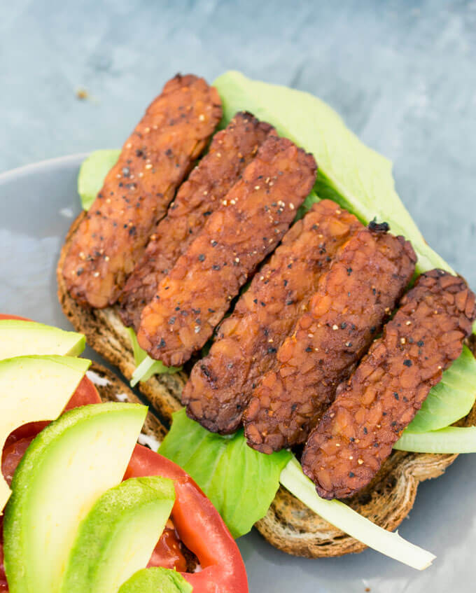 Close-up of the vegetarian tempeh bacon used in a vegan BLT on top of a piece of marbled rye bread