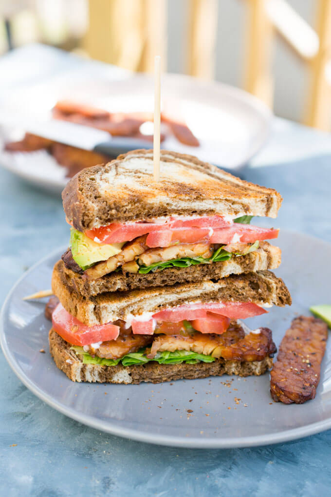A vegan BLT sandwich sliced in half on a plate with an extra piece of tempeh bacon next to it
