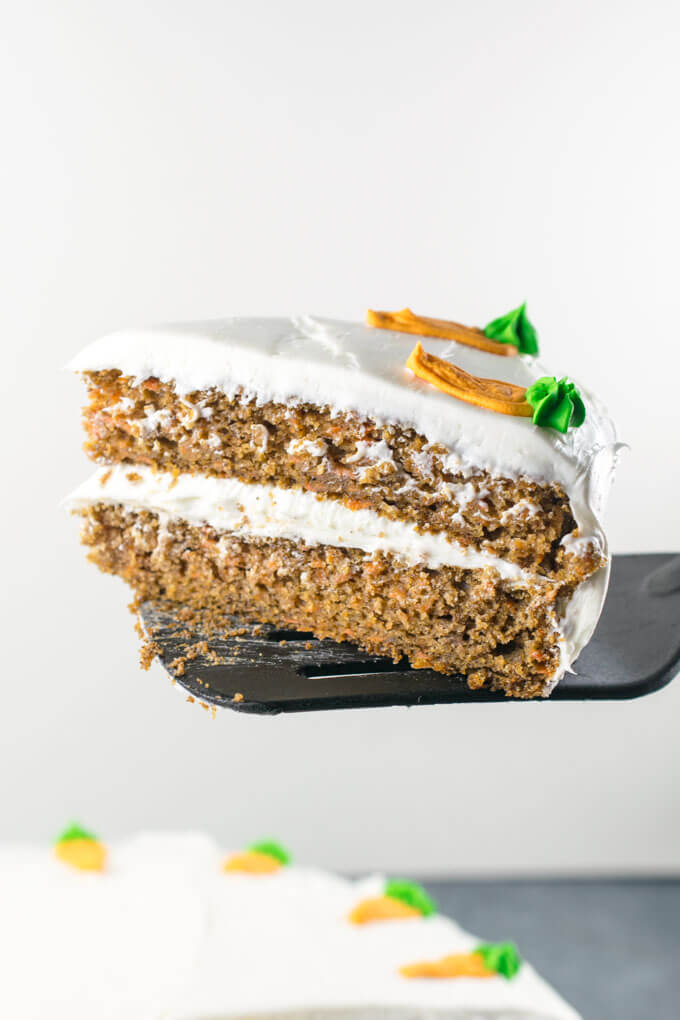 A slice of vegan two-layer carrot cake being held on a spatula in front of a white background