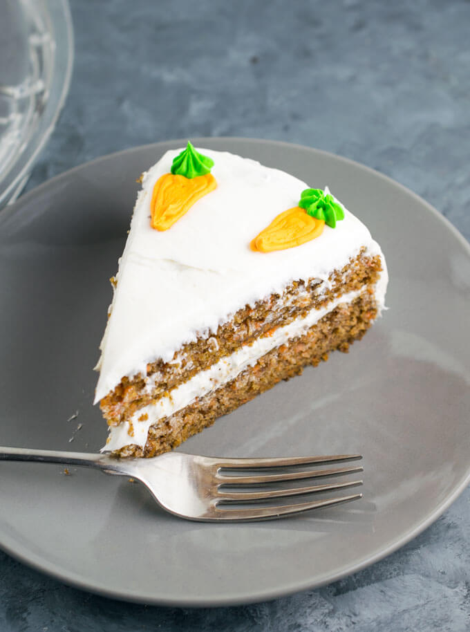 A slice of vegan carrot cake on a gray plate with a fork
