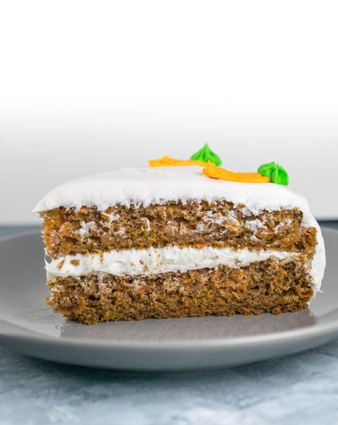 A slice of vegan carrot cake with white frosting between the two layers.