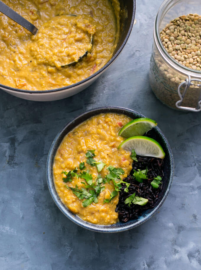 A small bowl of lentil curry with black forbidden rice, next to a pot of curry with ladle. In the background is a jar of dry green lentils.