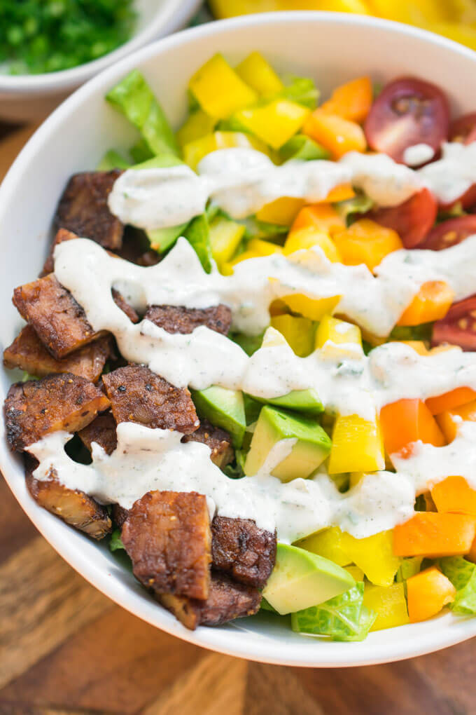 Vegan ranch drizzled over pieces of tempeh, lettuce, avocado, bell pepper, and tomatoes arranged in a white bowl