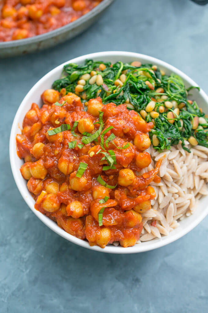 A bowl of chickpeas fra diavolo, whole wheat orzo, and sauteed spinach.