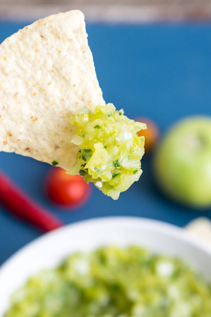 Close-up of green tomato salsa on a tortilla chip