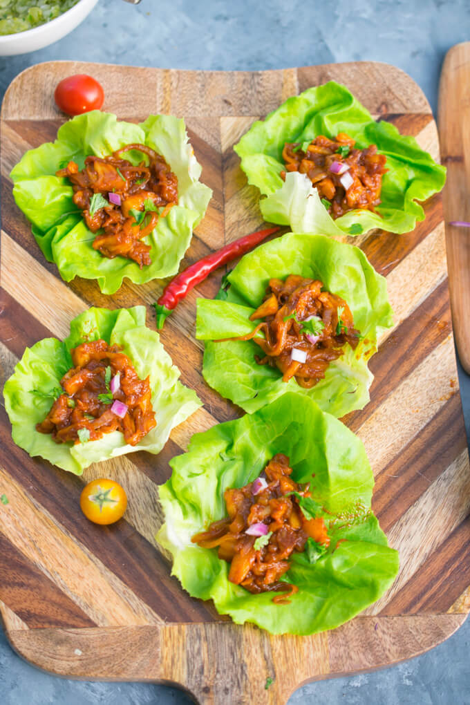 An arrangement of BBQ pulled pineapple lettuce wraps on a wooden cutting board