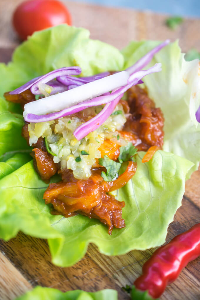 Close-up of a BBQ pulled pineapple lettuce wrap with salsa verde and a few pieces of shredded cabbage.