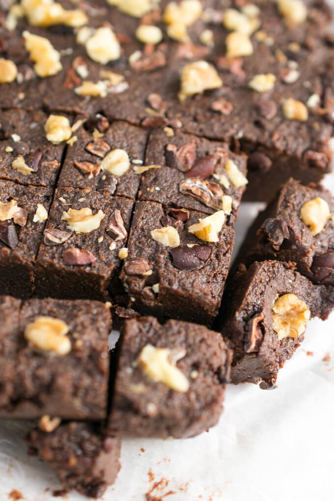 A slab of brownie batter freezer fudge cut into cubes and garnished with cacao nibs and chopped walnuts