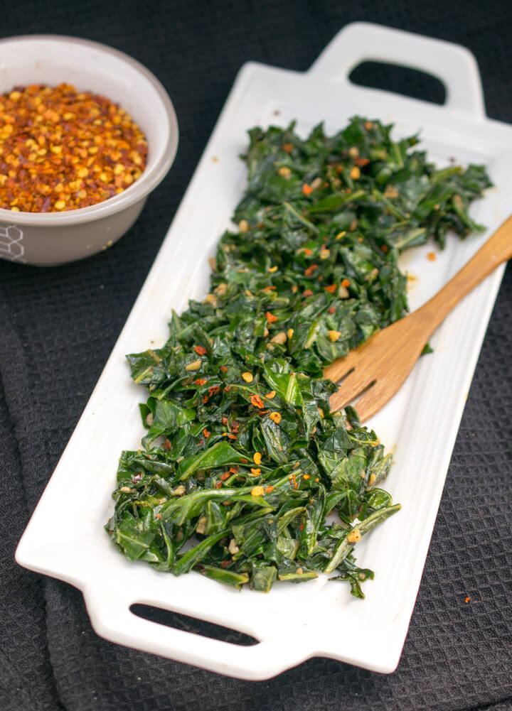 Sauteed collard greens on a plate next to a bowl of red pepper flakes