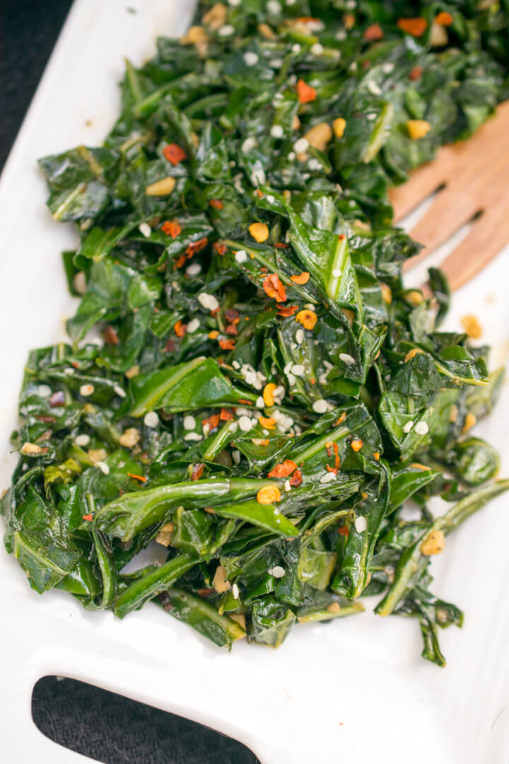 Close-up of sauteed collard greens on a white dish garnished with crushed red pepper and hemp seeds