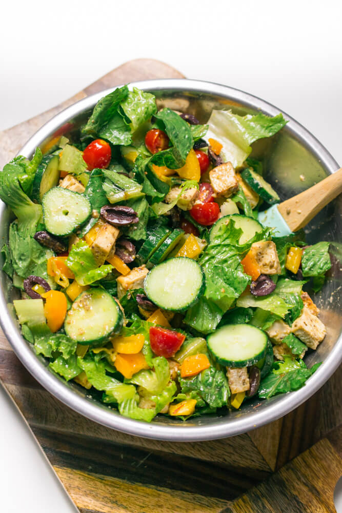 Vegan Greek salad in a mixing bowl after being tossed with dressing and romaine lettuce
