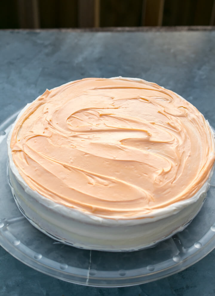 Overhead view of a two-layer vegan orange cake, frosted with orange and white frosting