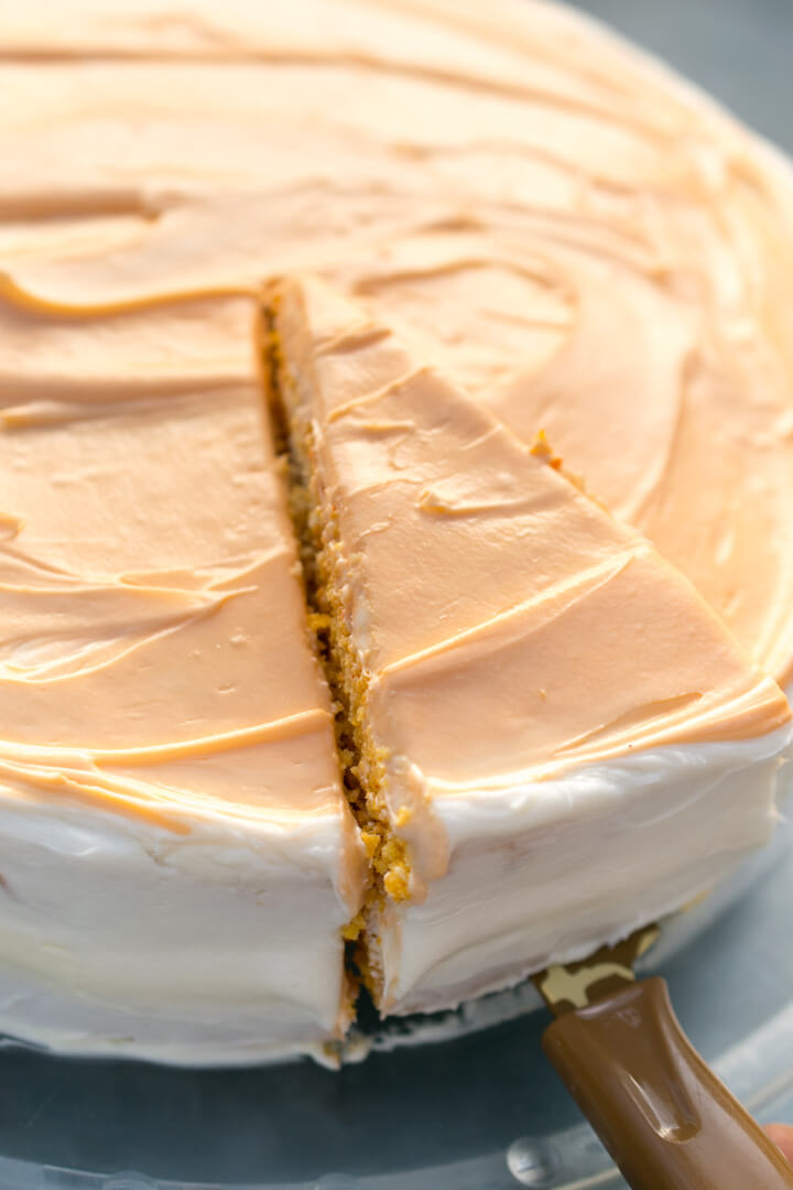 A slice being removed from a cake with dairy-free orange and white striped frosting