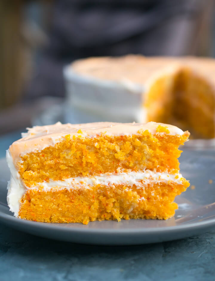 A slice of vegan orange cake showing two clean layers with white frosting in between.