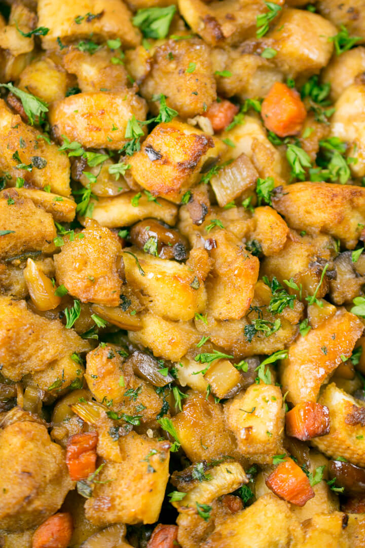 Close-up of a fresh batch of vegan stuffing showing the crispy top and golden brown color, garnished with parsley.