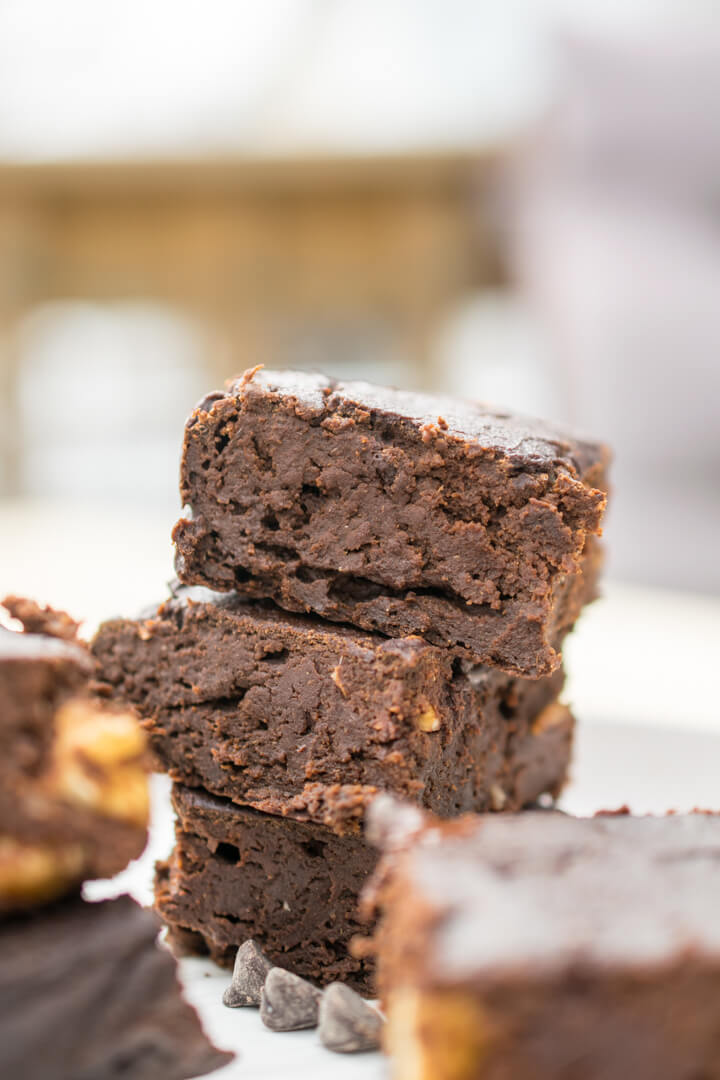 Close-up of three vegan sweet potato brownies showing a moist but fluffy texture.