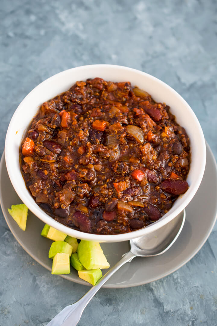A bowl of quinoa chili with no garnishes on a blue background with a spoon.