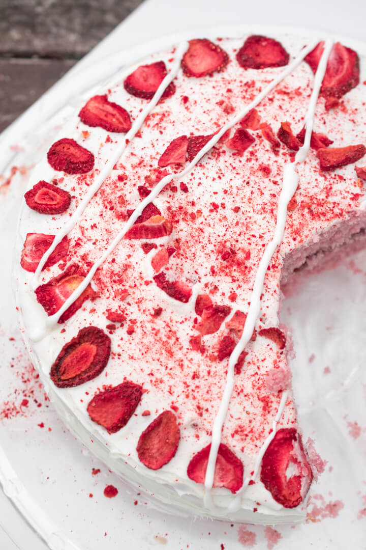 Overhead view of a vegan cake decorated with freeze-dried strawberries, strawberry powder, and white icing.